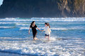 Two sisters running in ocean waves girls the of the together playing Royalty Free Stock Photography