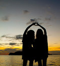 Two sisters silhouette making heart symbol Royalty Free Stock Photo