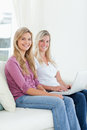 Two sisters sit on the couch with a laptop as they smile at the Stock Images