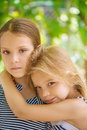 Two sisters are smiling on background of summer green park Stock Images