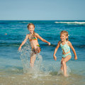 Two sisters splashing on the beach Royalty Free Stock Photo
