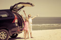 Two sisters standing near a car on the beach Royalty Free Stock Photo