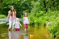 Two sisters and their mom playing with paper boats little in a river Royalty Free Stock Photo