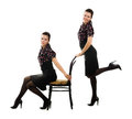Two sisters twins with a chair in retro style on white background Royalty Free Stock Image