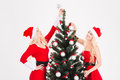 Two sisters twins in santa claus costumes decorating Christmas tree Royalty Free Stock Photo