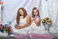 Two sisters in white dresses with flowers Royalty Free Stock Photography