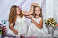 Two sisters in white dresses with flowers Stock Image