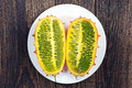 Two slices of fruit kiwano tropical on a white plate on table Stock Photos