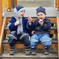 Two small boys brothers sitting steps children playground eating apples Stock Images