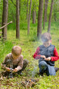 Two small boys lighting a fire in woodland setting to pile of leaves and twigs the grass as they enjoy day camping Royalty Free Stock Image