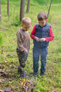 Two small boys lighting a fire in woodland setting to pile of leaves and twigs the grass as they enjoy day camping Royalty Free Stock Photo