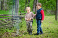 Two small boys lighting a fire in woodland setting to pile of leaves and twigs the grass as they enjoy day camping Royalty Free Stock Photography