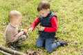 Two small boys lighting a fire in woodland setting to pile of leaves and twigs grass as they enjoy day camping nature Stock Images