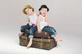 Two small brothers sitting on the suitcases cute Stock Photo