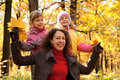 Two small girls with mother in autumnal park Stock Image