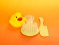 Two small hairbrushes and a rubber duckling Royalty Free Stock Photo