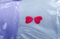 Two small red heart on a white cloth with a purple stripe Royalty Free Stock Photo