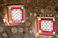 Two small red stained glass windows in stone wall Stock Images