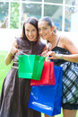 Two smiley girls with purchases Royalty Free Stock Photography
