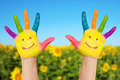 Two smiley hands in sunny summer s day on a background of field of sunflowers and blue sky holidays concept Royalty Free Stock Photo