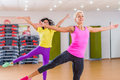 Two smiling athletic women doing aerobic dancing exercises holding their arms sideward indoors in fitness center.