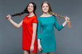 Two smiling beautiful women standing and showing their long braids Royalty Free Stock Photo