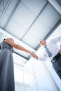 Two smiling business people shaking hands low angle view of Royalty Free Stock Images