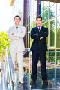 Two smiling businessmen with arms crossed standing on the building background Stock Photography