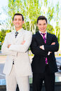Two smiling businessmen with arms crossed standing outdoors Royalty Free Stock Photos