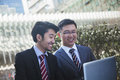 Two smiling businessmen looking at laptop together outdoors in beijing Stock Photography