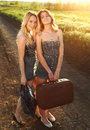 Two smiling girlfriend with suitcase at countryside on lonely road in sunset rays Royalty Free Stock Photos