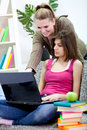 Two smiling girls doing homework using a laptop. Stock Image