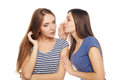 Two smiling girls friends whispering gossip over white background Stock Photography