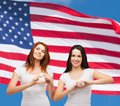 Two smiling girls showing heart with hands friendship patriotic and happy people concept in white blank t shirts Royalty Free Stock Photo