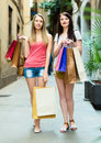 Two smiling girls walking with purchases in european city Stock Images