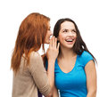 Two smiling girls whispering gossip friendship happiness and people concept Royalty Free Stock Photos