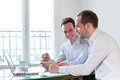 Two smiling happy business men working on project Royalty Free Stock Photo
