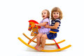 Two smiling little girls riding on a toy wooden horse  Stock Photos
