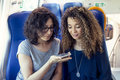 Two smiling lovely girls using a smartphone Royalty Free Stock Photo