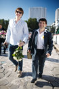Two smiling men walking down a street groom and his friend one carrying flowers and the other in suit wearing buttonhole Stock Photos