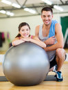 Two smiling people with fitness ball sport training gym and lifestyle concept in the gym Royalty Free Stock Image