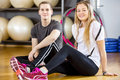 Two smiling people having a break at the fitness gym happy young women and men taking from training team resting after workout Royalty Free Stock Photos