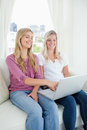 Two smiling sisters watch a tv show on the laptop Royalty Free Stock Image