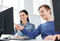 Two smiling students having discussion education technology school and people concept in computer class at school Stock Images