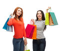 Two smiling teenage girls with shopping bags sale and gifts concept Royalty Free Stock Photos
