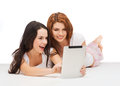 Two smiling teenage girls with tablet pc computer technology internet and entertainment concept girsl in pajamas Stock Images