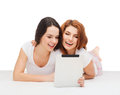 Two smiling teenage girsl with tablet pc computer Royalty Free Stock Photo
