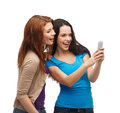 Two smiling teenagers with smartphone technology friendship and people concept Stock Photography
