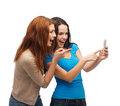 Two smiling teenagers with smartphone technology friendship and people concept pointing finger at Royalty Free Stock Photos