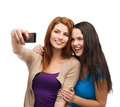 Two smiling teenagers with smartphone technology friendship and people concept taking picture camera Stock Image